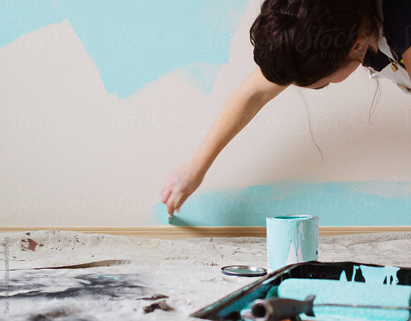 young woman leans to paint edge of wall behind open can of paint by Tana Teel for Stocksy United