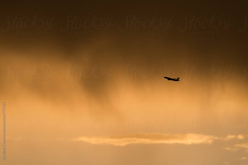 Commercial flight taking off at sunset by Luca Pierro for Stocksy United