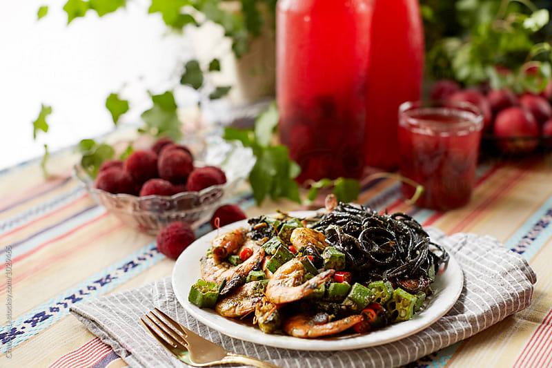 Pesto pasta and fresh cranberry juice at the table by ChaoShu Li for Stocksy United