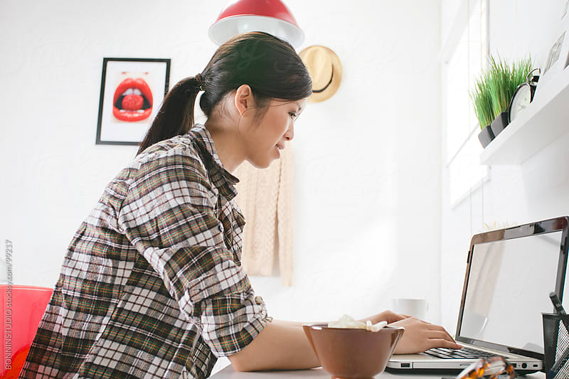 Casual asian woman working on a laptop at home. by BONNINSTUDIO for Stocksy United