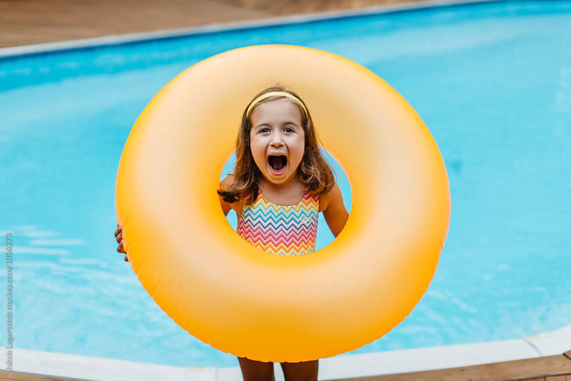 Cute girl showing her excitement over her inner tube by Jakob for Stocksy United