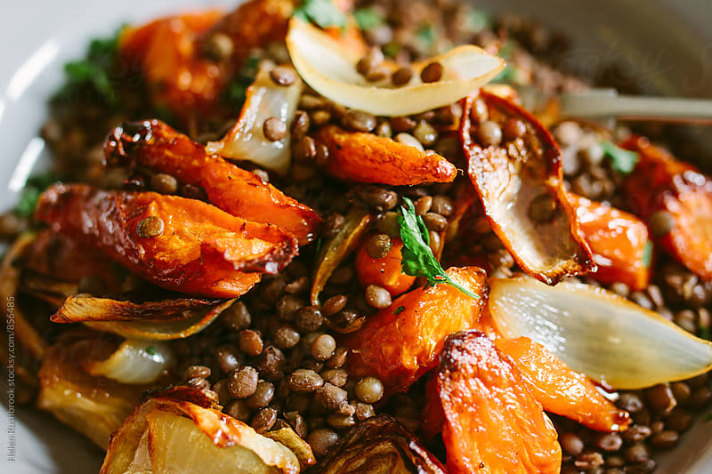 Roasted root vegetables and puy lentils. by Helen Rushbrook for Stocksy United