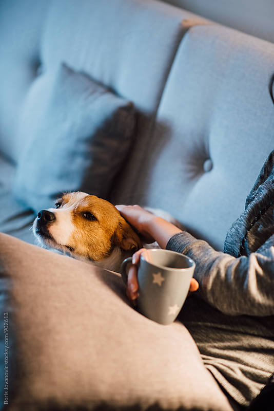 Woman cuddling a dog and drinking tea by Boris Jovanovic for Stocksy United