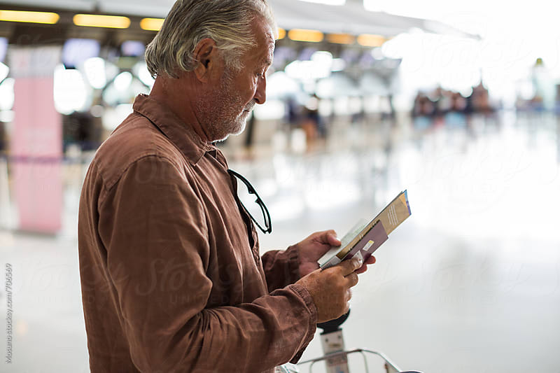 Senior Man Checking His Ticket at the Airport by Mosuno for Stocksy United