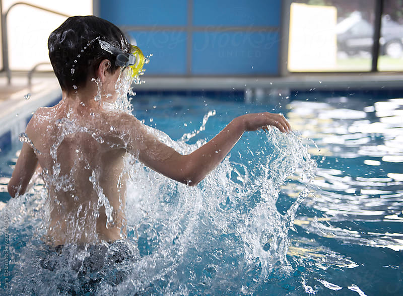 Boy wearing swimming mask splashes in an indoor pool by Cara Dolan for Stocksy United