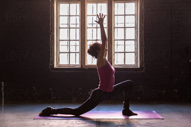 Woman extending her arms upwards in a yoga position  by Jovo Jovanovic for Stocksy United