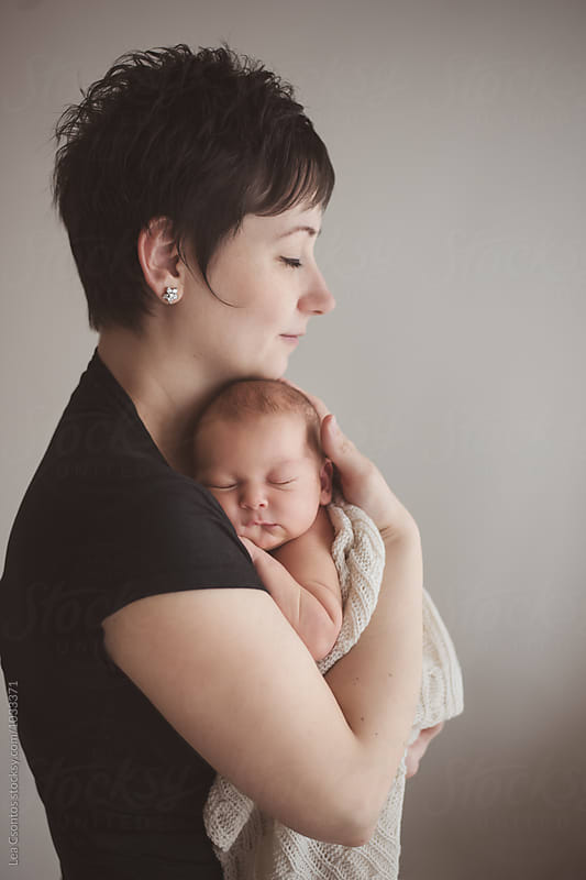 Mother holding tight her newborn baby by Lea Csontos for Stocksy United