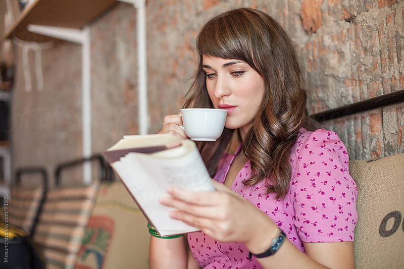 Woman Reading a Book and Drinking Coffee by Mosuno for Stocksy United