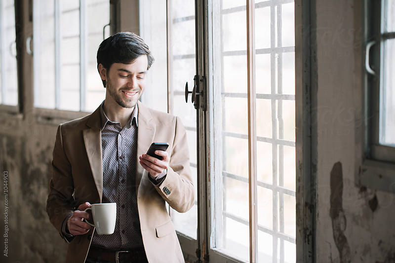 Elegant man with cup of coffee using cell by Alberto Bogo for Stocksy United