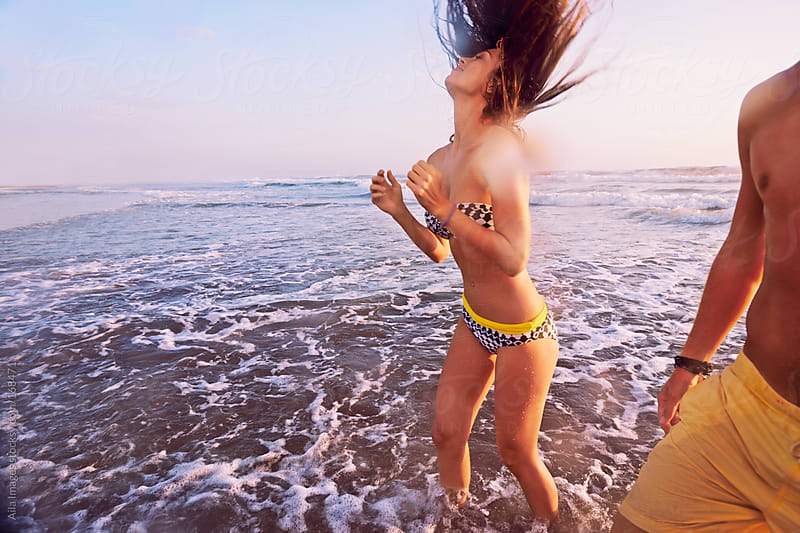 Beautiful Girl flicking her hair after swimming on the beach by Aila Images for Stocksy United