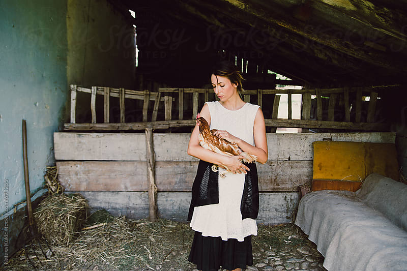 Portraits of a woman in the countryside holding chicken by Natasa Kukic for Stocksy United