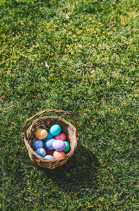 Basket of colorful Easter eggs in the grass by Lindsay Crandall for Stocksy United