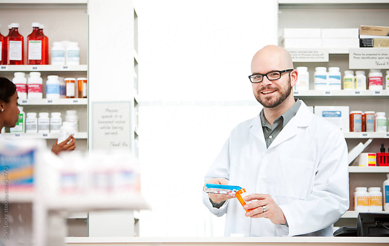 Pharmacy: Cheerful Pharmacist Fills Prescription by Sean Locke for Stocksy United