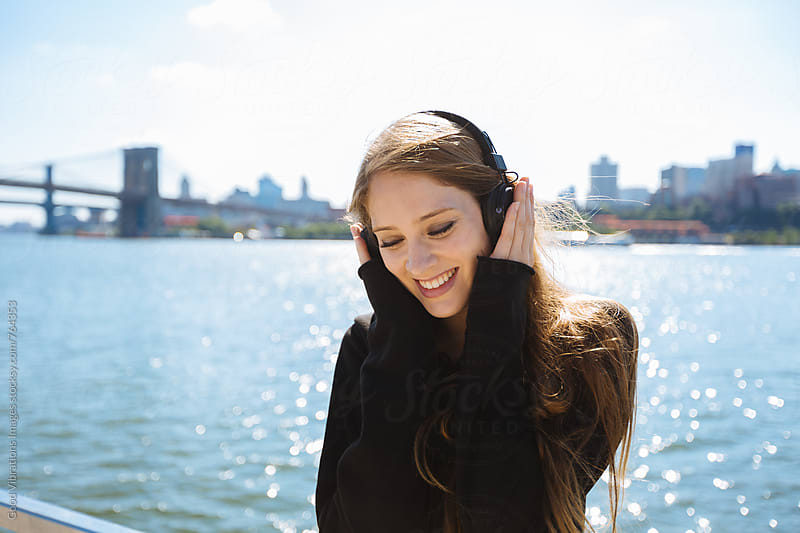 Smiling woman listening music in NYC by Good Vibrations Images for Stocksy United