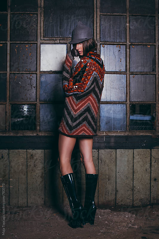 Beautiful woman wearing a colorful sweater and a hat in abandoned storage house by Maja Topcagic for Stocksy United