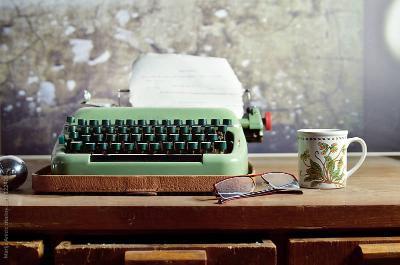 Vintage retro typewriter and cup of coffee with cookie on wooden desk by Marija Anicic for Stocksy United