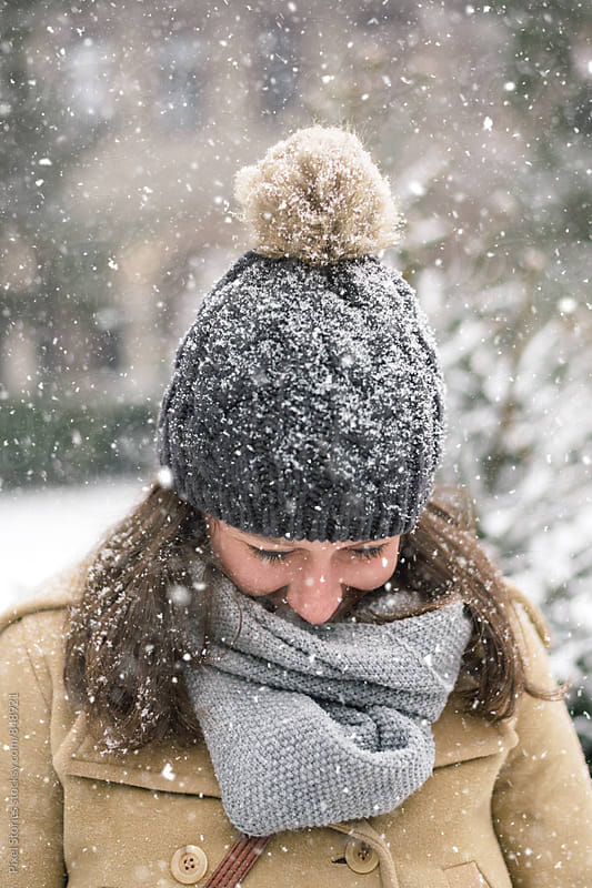 Smiling young woman during a snow storm  by Pixel Stories for Stocksy United