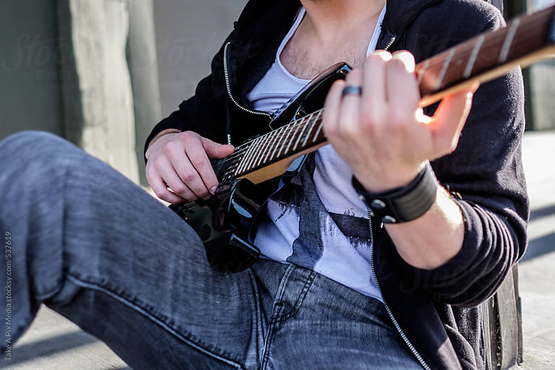 Man sitting playing a guitar by Suprijono Suharjoto for Stocksy United