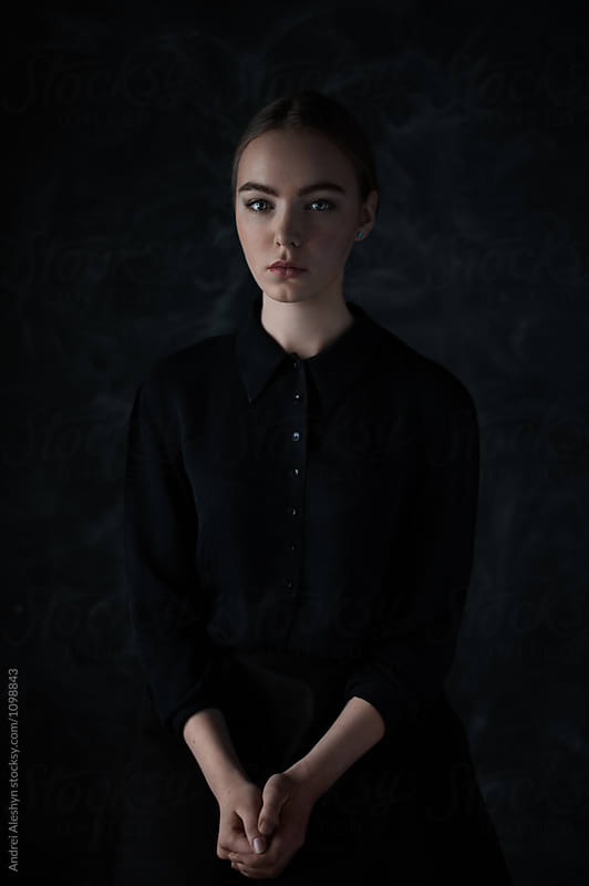 portrait of a beautiful young model in a dark dress in the studio by Andrei Aleshyn for Stocksy United