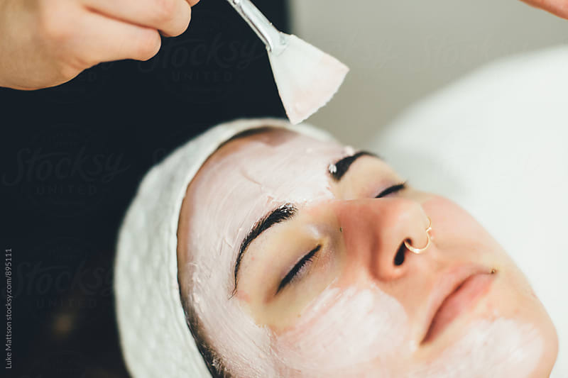 Esthetician Brushing Young Woman's Face With Facial Mask by Luke Mattson for Stocksy United