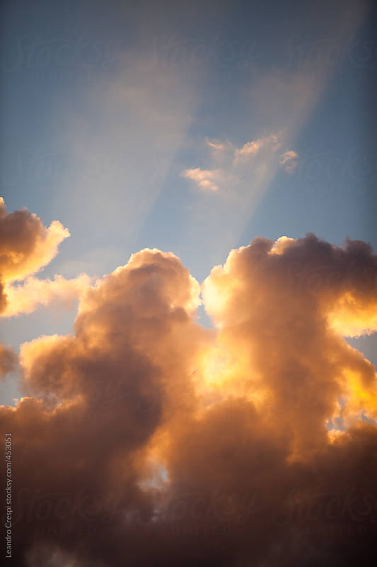 Cloudy blue sky, orange sunset by Leandro Crespi for Stocksy United