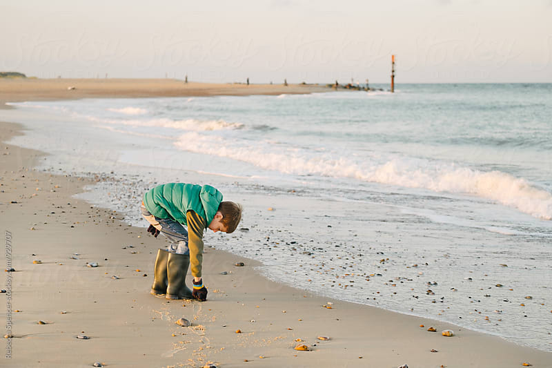 Child collects pebbles from the sand by Rebecca Spencer for Stocksy United
