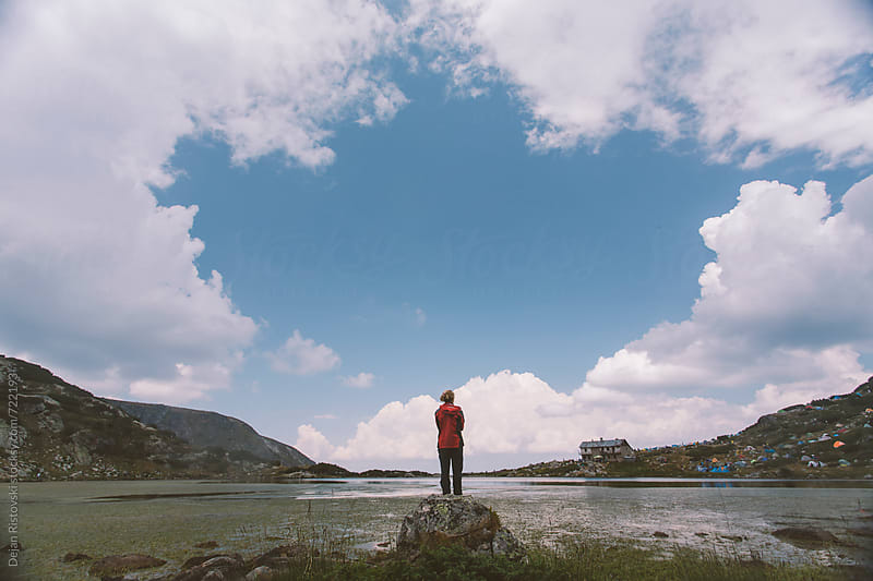 A woman standing on a mountain lake by Dejan Ristovski for Stocksy United