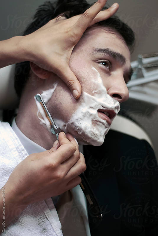 Man receives straight razor shave by Cara Dolan for Stocksy United