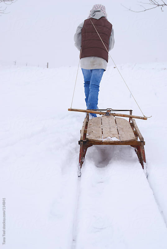 A young girl pulls an old wooden sled through the snow by Tana Teel for Stocksy United