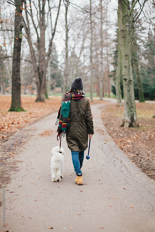 Woman walking her dog through the park  by Marija Mandic for Stocksy United