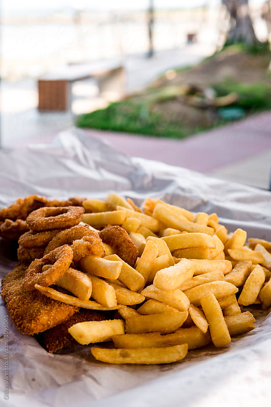 takeaway fish and chips on a picnic table by the sea by Gillian Vann for Stocksy United