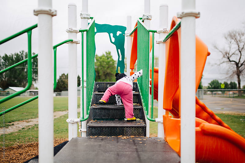 Toddler girl climbing up stairs at playground by Jessica Byrum for Stocksy United