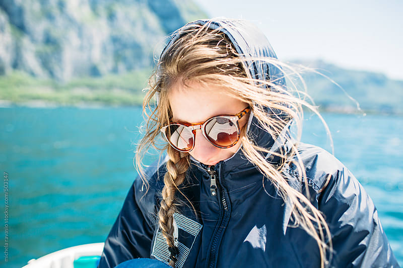 Girl with cap sitting on the boat on the lake by michela ravasio for Stocksy United