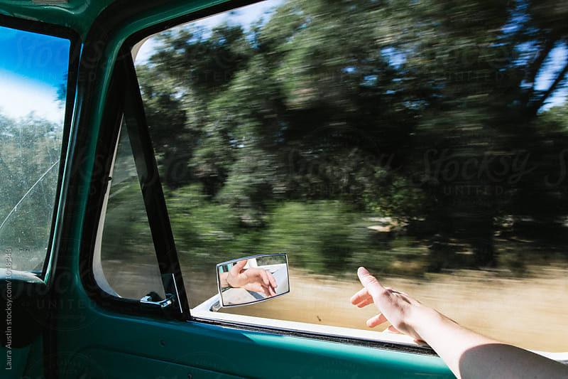 Girl Holding Hand Outside Of Truck On A Road Trip by Laura Austin for Stocksy United