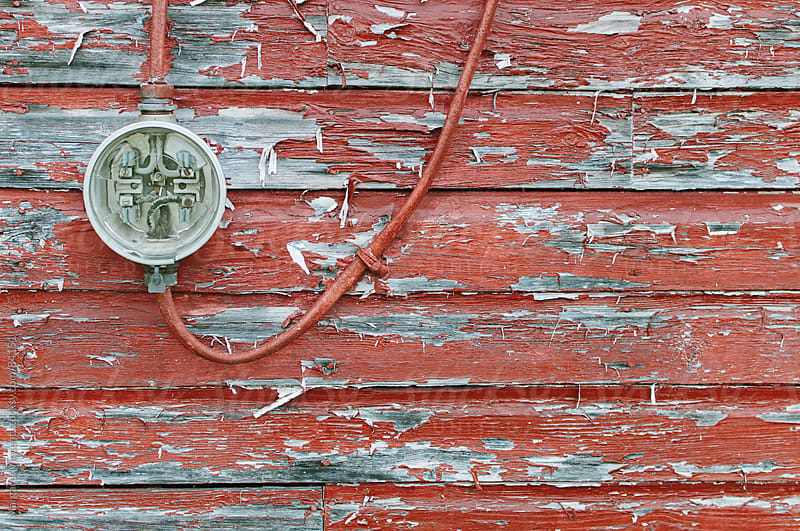 meter on weathered red wall by Margaret Vincent for Stocksy United