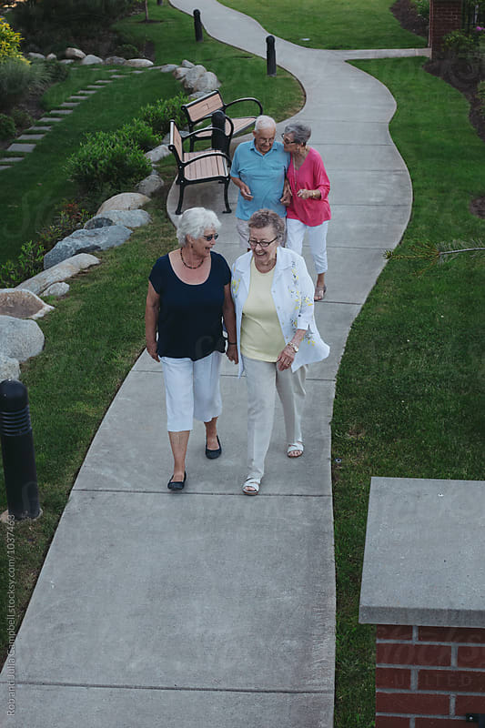 Group of happy caucasian seniors walking and talking outside garden path by Rob and Julia Campbell for Stocksy United