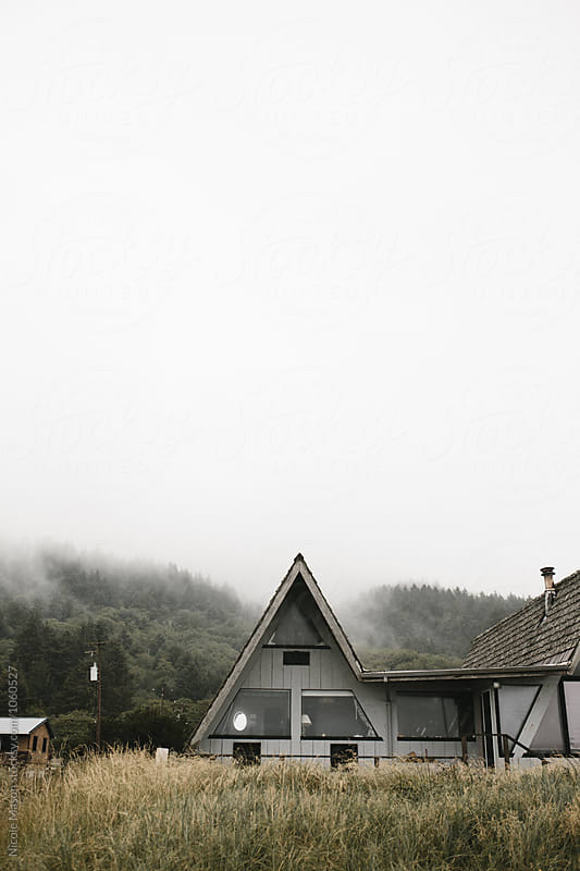 home on the coast on gloomy cloudy day by Nicole Mason for Stocksy United