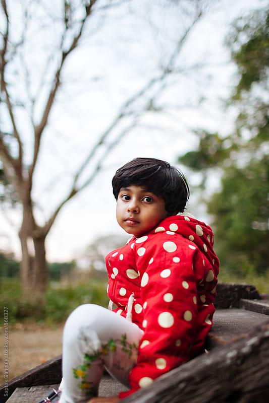 Child looking at the camera in a pensive mood by Saptak Ganguly for Stocksy United
