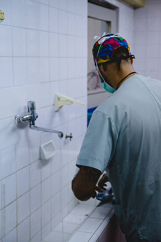 Surgeon washing hands before surgery by Leandro Crespi for Stocksy United
