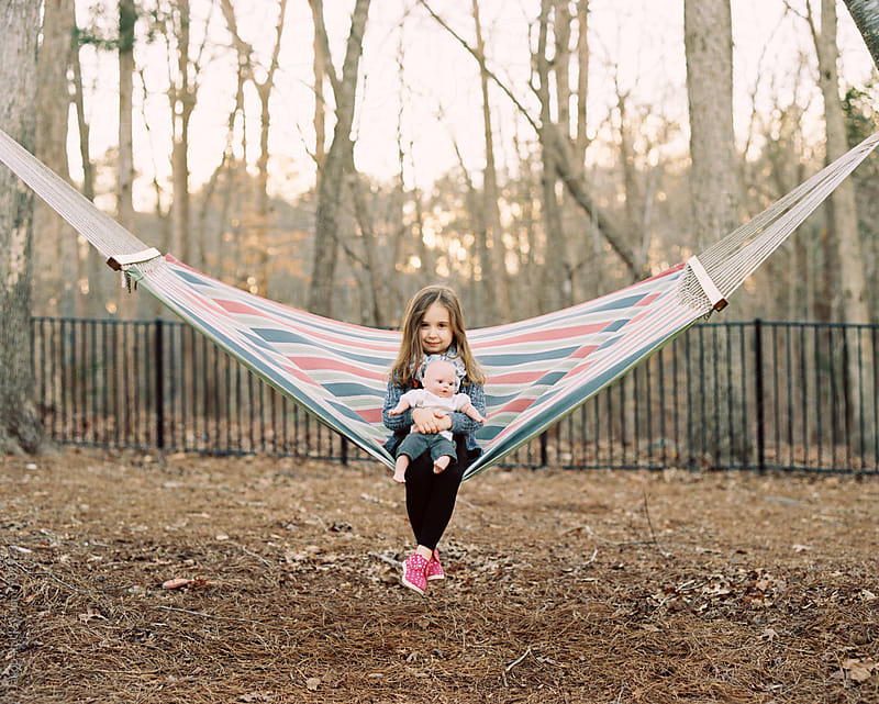 Cute young girl sitting on a hammock with her doll by Jakob for Stocksy United