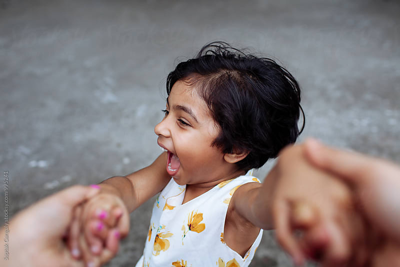 Little girl spin holding her mothers hand,happy family by Saptak Ganguly for Stocksy United