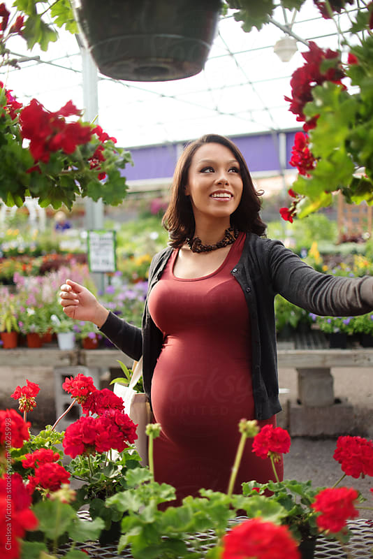 A pregnant woman shopping for flowers in a nursery by Chelsea Victoria for Stocksy United