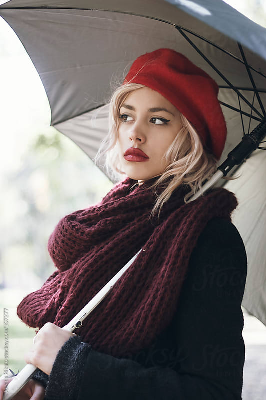Beautiful woman holding umbrella in park by Jovana Rikalo for Stocksy United