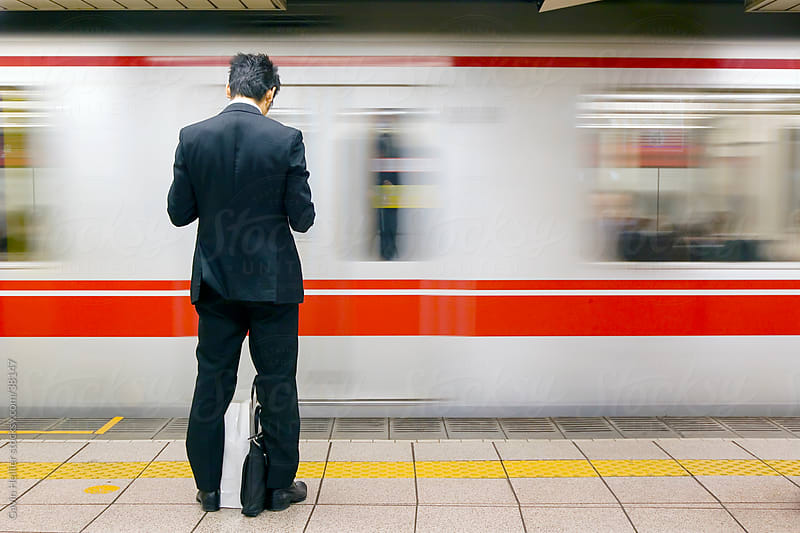 Asia, Japan, Honshu, Tokyo, Tokyo Subway, business man in front of passing subway train - blurred motion by Gavin Hellier for Stocksy United