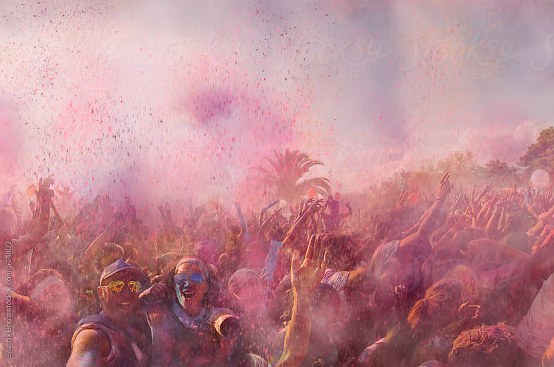 A crazy couple taking a selfie at a concert where holi powder is flying in the air by Beatrix Boros for Stocksy United