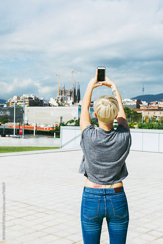 Woman taking a photo to Sagrada Familia from far away.  by BONNINSTUDIO for Stocksy United