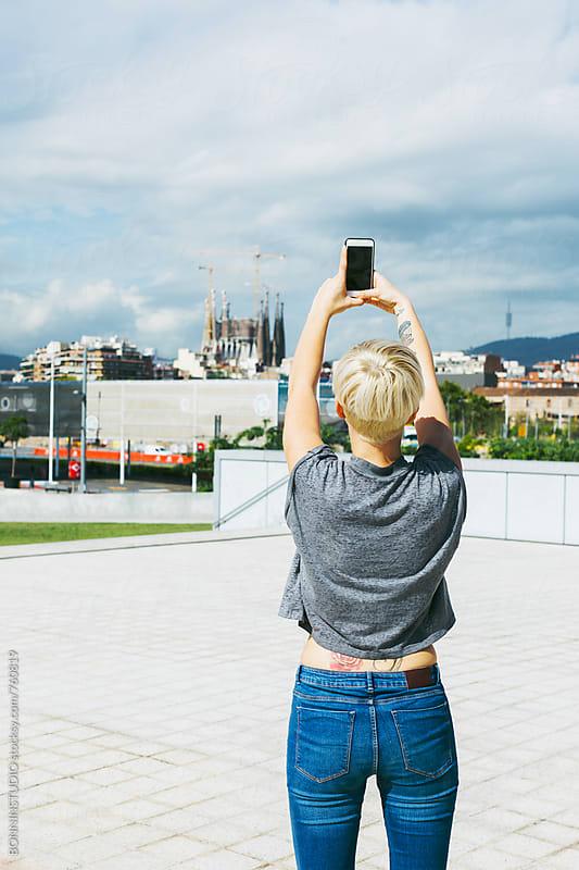 Woman taking a photo to Sagrada Familia from far away.  by BONNINSTUDIO for Stocksy United
