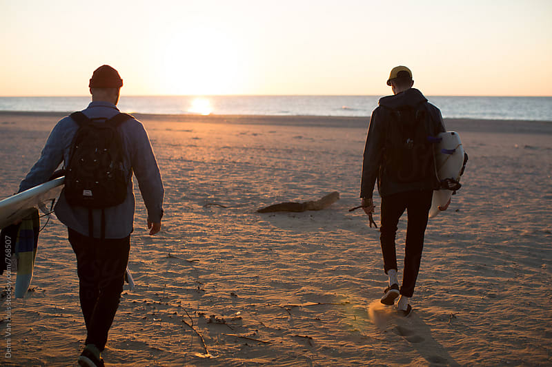Friend walking into the sunset with their surfboards. by Denni Van Huis for Stocksy United