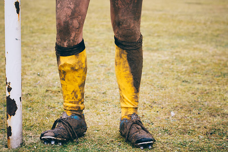 The muddy legs of a rugby player by Helen Rushbrook for Stocksy United