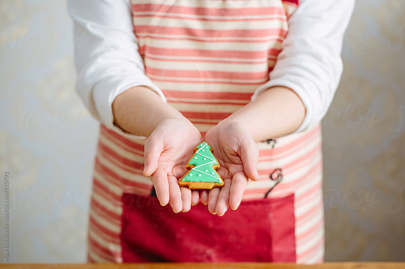 Baker holding a Christmas tree cookie by MaaHoo Studio for Stocksy United